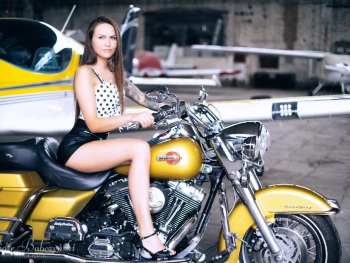 Girl with motorcycle and plane in the background