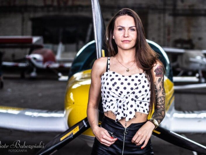 Girl with a motorcycle and a plane in the background